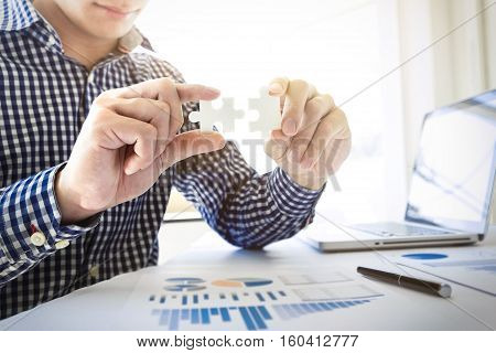 business people assembling holding two blank jigsaw puzzle pieces in his hands conceptual of solving a problem growth and development