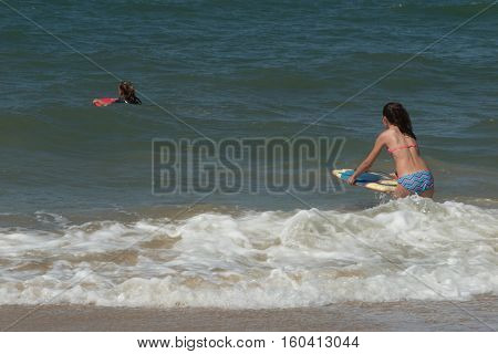 Two Teenager Girl In The Beach Playing Body Board