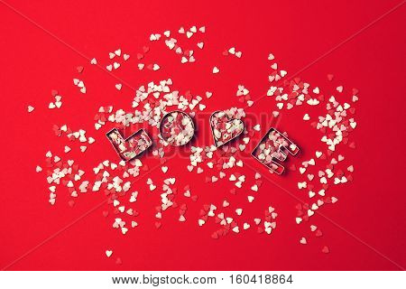 Love concept with letters LOVE and sweethearts on a red background. Top view with copy space