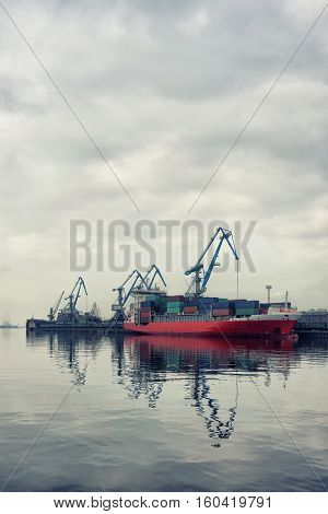 Cargo ship at dusk with cloudy sky in the port of Riga in the background of cars and cranes with a load