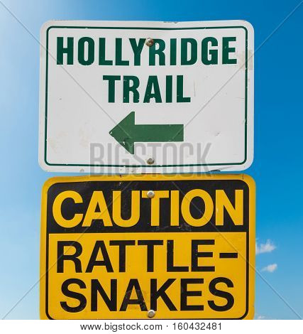 HOLLYRIDGE TRAIL and CAUTION RATTLE SNAKES signs under a blue sky