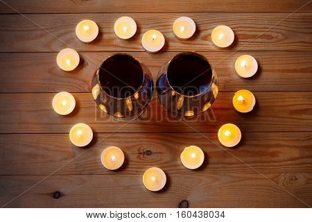 Glasses of wine with candles on wooden background