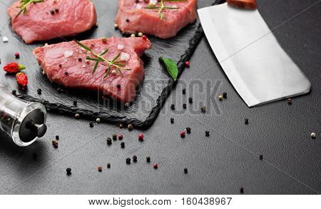 Raw Beef Meat With Butcher Knife On Slate Plate.scattered Black Pepper, Chili .dark Bakcground.selec
