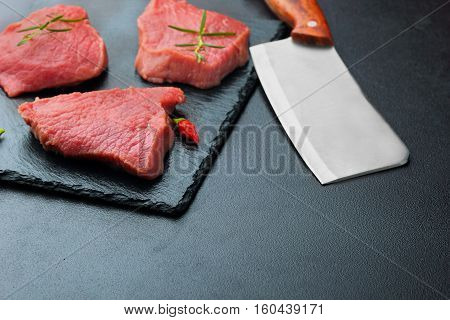 Raw Beef Meat With Butcher Knife On Dark Bakcground.selective Focus . Copy Space