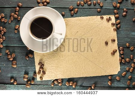 A cup of black coffee on a piece of old parchment with copyspace, shot from above on a wooden boards texture, with beans scattered around. A horizontal design template for a cafe or shop