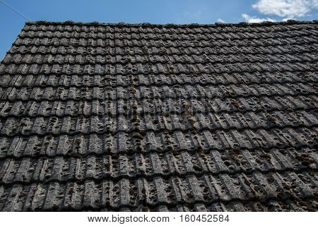 Close Up Of Aged Roofing Tiles On Old House In Village. A Lot Of Moss On Tiled Roof Of Hovel. Countr