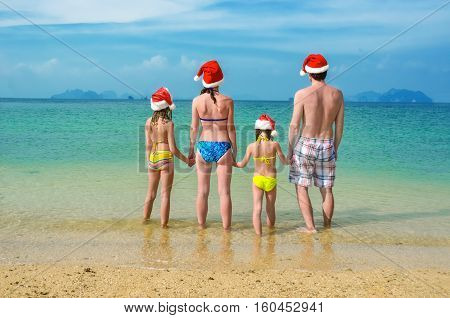 Family vacation on Christmas and New Year holidays, happy parents and children in santa hats have fun on beach, travel with kids