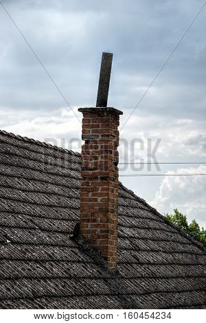 Aged roofing tiles with chimney on old house in village. A lot of moss on tiled roof of hovel against blue cloudy sky. Countryside scene