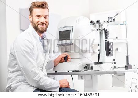 Portrait of handsome eye doctor sitting with ophthalmologic device in the cabinet
