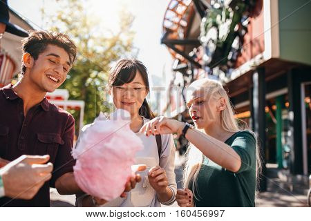 Group of friends eating cotton candy in amusement park. Young man and women sharing cotton candy floss at carnival.