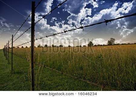 Clouds in sky and Farmers Fence and field