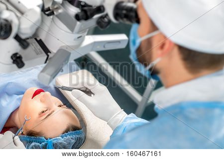 Surgion operating eye of female patient with surgical tools in the operating room