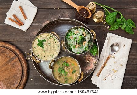 Vegan or vegetarian restaurant dishes top view, hot spicy indian soups and rice vermicelli in copper bowls. Traditional indian cuisine meal assortment on wood background. Healthy eastern local food