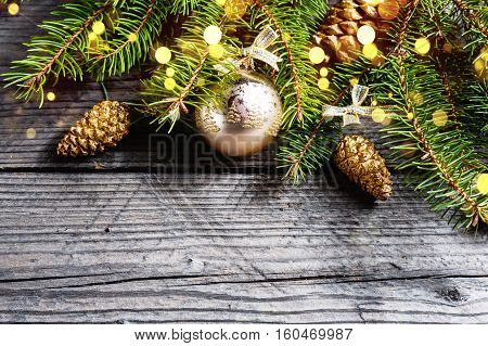 Christmas background. Green Fir tree branches with pine cones, gold snowflakes, ball and bokeh on wooden background. Copy spase