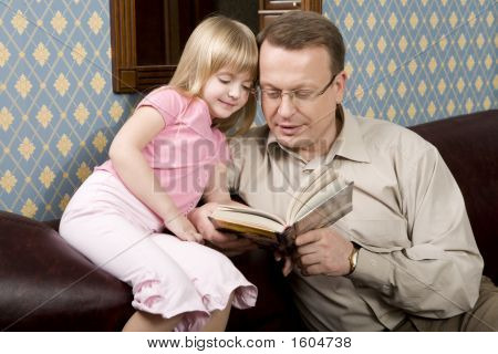 Father And Daughter Are Reading A Book