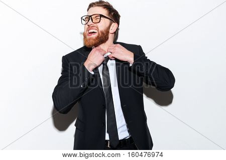 Bearded Business man in glasses unties his tie and looking aside. Isolated gray background