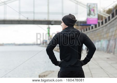 Back view of handsome young man athlete standing with hands on hips outdoors