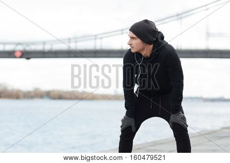 Thoughtful young man with earphones resting after running and thinking outdoors
