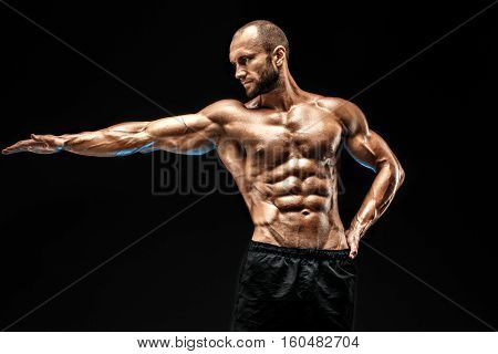 Strong bald bodybuilder with six pack. Strong bodybuilder man with perfect abs, shoulders, biceps, triceps and chest, personal fitness trainer flexing his muscles in blue, red smoke