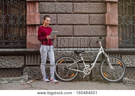 Young woman dressed in sweater standing near her bicycle on the street and using tablet. Look at tablet.