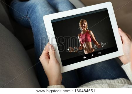Woman watching sport training online on tablet. Fitness and sport blog.