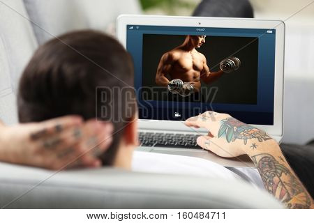 Man watching sport training online on laptop. Fitness and sport blog.