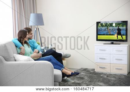 Young couple watching football game on television at home. Leisure and entertainment concept.