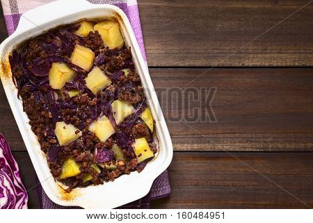 Baked red cabbage apple mincemeat and potato casserole in dish photographed overhead on dark wood with natural light (Selective Focus Focus on the top of the dish)