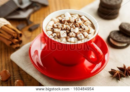Cup of cocoa drink with marshmallow on table. Hot chocolate with sandwich cookies for breakfast.