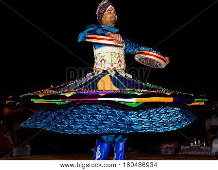 DUBAI UAE - APRIL 20 2012: A local citizen performing traditional folk dance at night as part of the desert safari camp experience