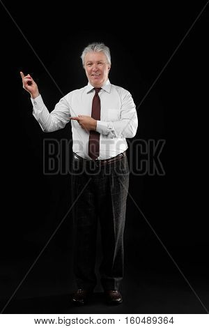 Senior businessman on black background