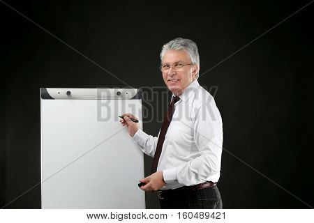 Senior businessman with flip chart on black background