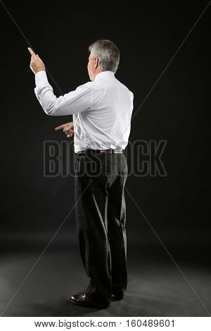 Senior businessman standing back on black background