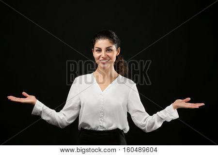 Young businesswoman on black background