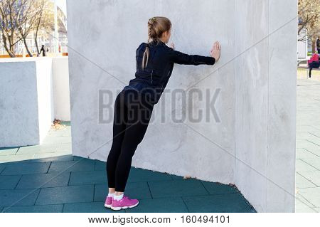 Fitness woman doing push-ups at the wall back view