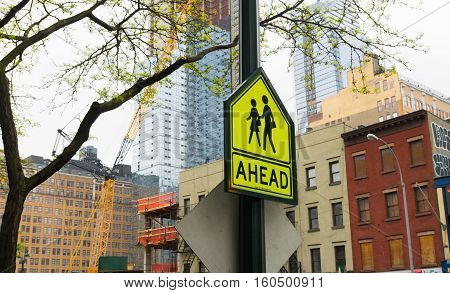 yellow traffic sign in New York of school zone with crossing children with the word ahead