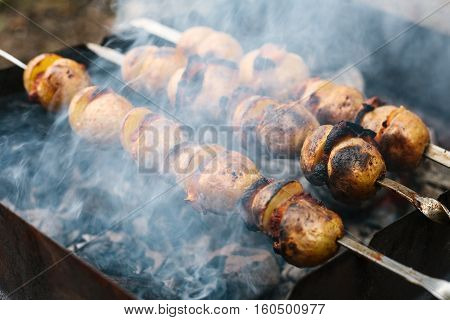Fried potatoes with bacon on skewers. The concept of eating outdoors in the weekend.