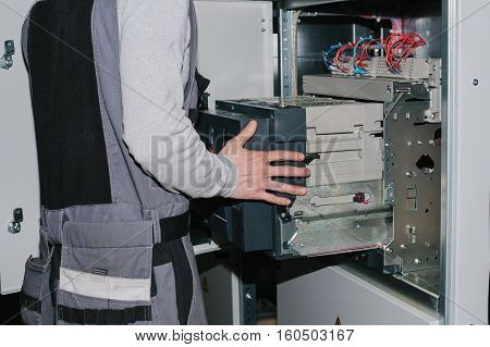 Electrician near the low voltage cabinet. Uninterrupted power supply. Electricity.