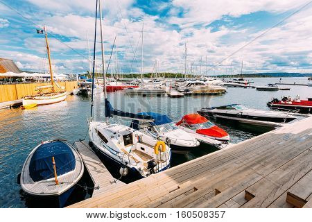 Oslo, Norway. The Wooden Sea Pier With Moored Boats And Yachts At Aker Brygge District. The Seascape Of Harbour And Quays In Summer Sunny Day Under Scenic Cloudy Sky.