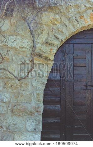 The facade of an old and rustic house. Medieval door
