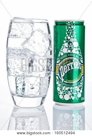 LONDON UK - DECEMBER 06 2016: Glass with ice and tin of Perrier sparkling water. Perrier is a French brand of natural bottled mineral water sold worldwide.