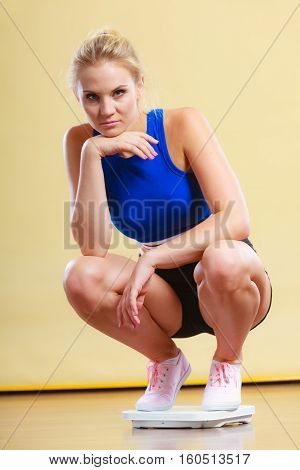 Upset Sporty Woman On Weight Scale.