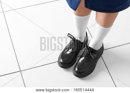 Feet of schoolgirl in uniform indoors
