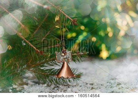 Celebratory background with an angel Christmas toy hanging on fir branch blurred background with a large bright bokeh