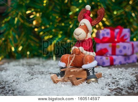 Christmas toy deer in holiday clothes on wooden sleigh among snow blurred background Christmas tree
