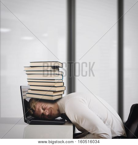 Businessman on laptop with a pile of books on head. Oppressed by work concept