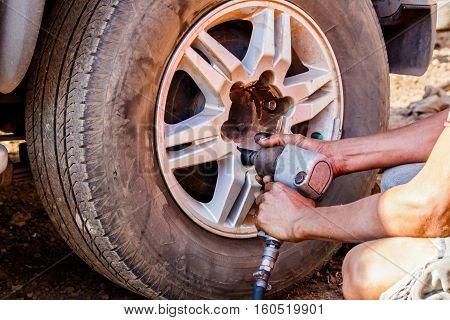 Auto mechanic removing the wheel with an air gun to recap.