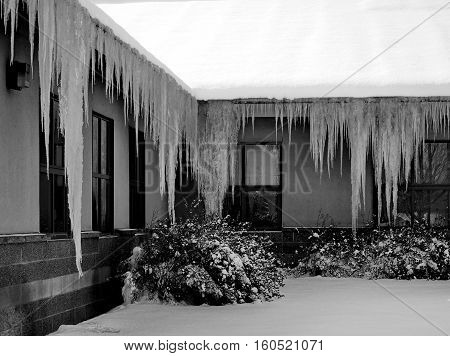 Gigantic ice sickles hanging from the roof of a building in Central Oregon on a winter day.