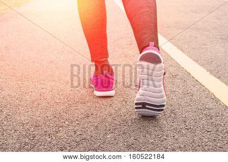 Athlete runner feet running on road closeup on shoe.