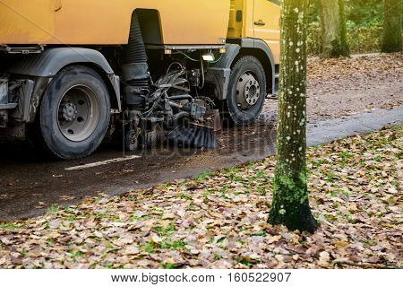 Lower part of orange street sweeper machine cleaning the street after in fall from fallen foliage